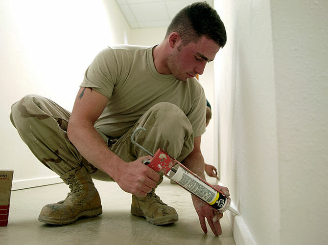 Mississauga house painters putting caulk on baseboard